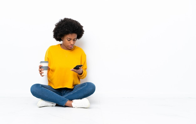 Young african american woman sitting on the floor holding coffee to take away and a mobile
