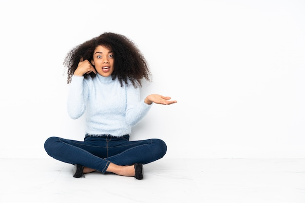 Young african american woman sitting on the floor making phone gesture and doubting