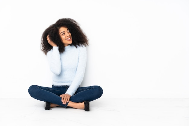 Young african american woman sitting on the floor thinking an idea