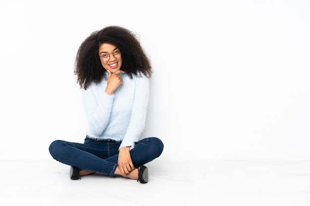 Young african american woman sitting on the floor with glasses and smiling