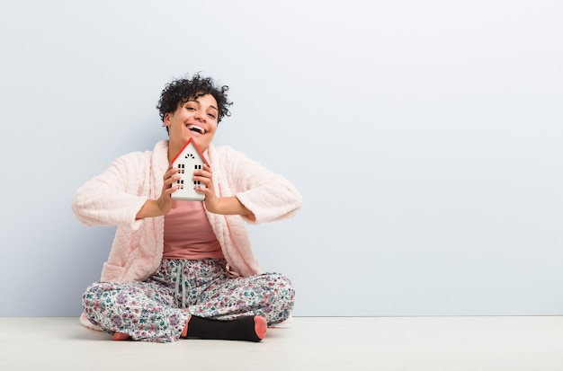 家のアイコンを持って座っている若いアフリカ系アメリカ人女性