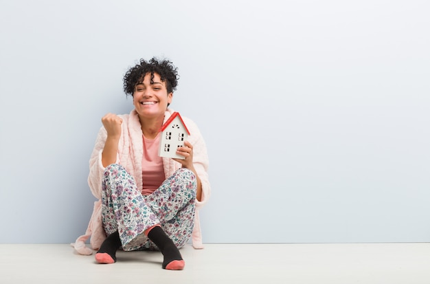 Young african american woman sitting holding a house icon