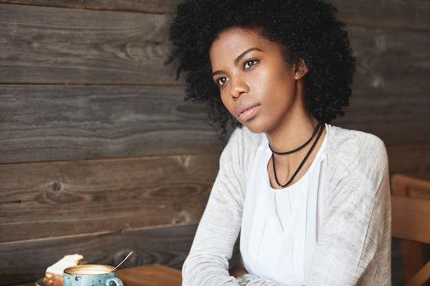 カフェに座っている若いアフリカ系アメリカ人女性