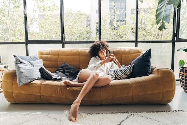편안한 소파에 앉아 친구에게 문자 메시지를 보내는 젊은 아프리카계 미국인 여성 home technology