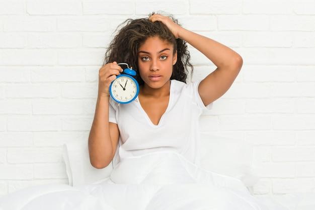 ショックを受けている目覚まし時計を保持しているベッドに座っている若いアフリカ系アメリカ人女性は、彼女が重要な会議を思い出しました。