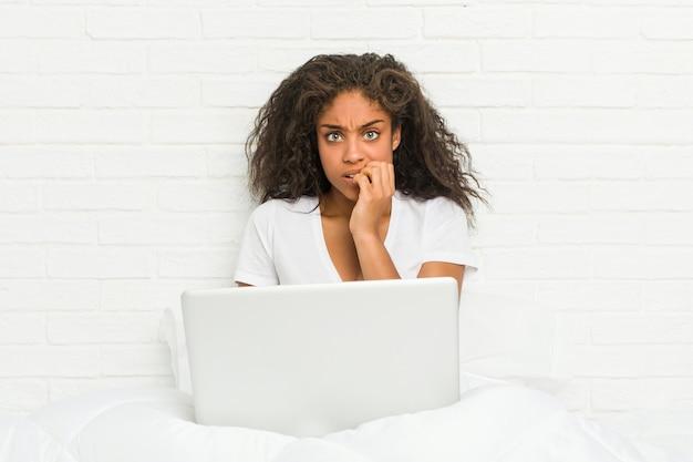神経質で非常に心配しているラップトップの爪を噛んでベッドに座っている若いアフリカ系アメリカ人の女性。