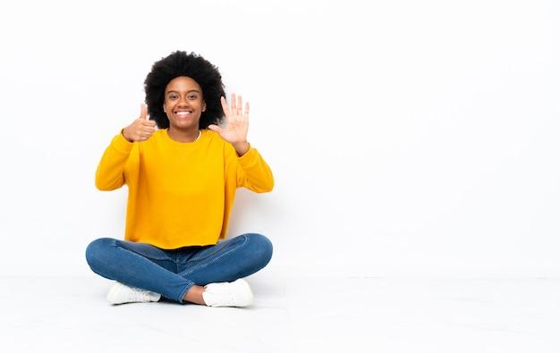 Молодая афро-американских женщина, сидя на полу, считая шесть с пальцами