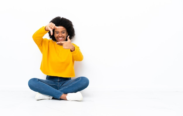 顔に焦点を当てて床に座っている若いアフリカ系アメリカ人の女性。フレーミングシンボル