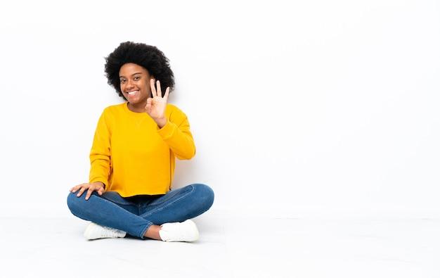 幸せな床に座って、指で3つを数える若いアフリカ系アメリカ人女性