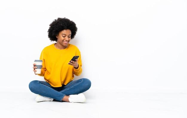 Молодая афроамериканская женщина сидит на полу, держа кофе на вынос и мобильный