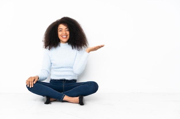 広告を挿入するために手のひらに架空のcopyspaceを保持している床に座っている若いアフリカ系アメリカ人女性
