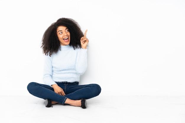 손가락을 들어 올리는 동안 솔루션을 실현하기 위해 바닥에 앉아 젊은 아프리카 계 미국인 여자