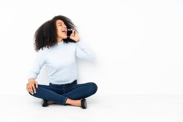 Молодая афро-американская женщина сидит на полу и разговаривает по мобильному телефону