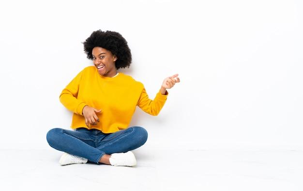 ギターのジェスチャーを作る床に座っている若いアフリカ系アメリカ人女性
