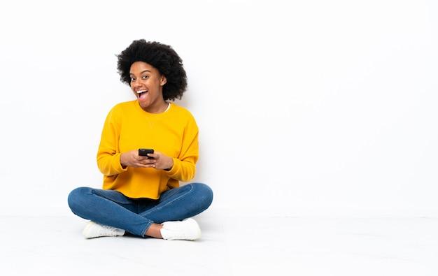 Молодая афроамериканец женщина сидит на полу удивлен и отправив сообщение