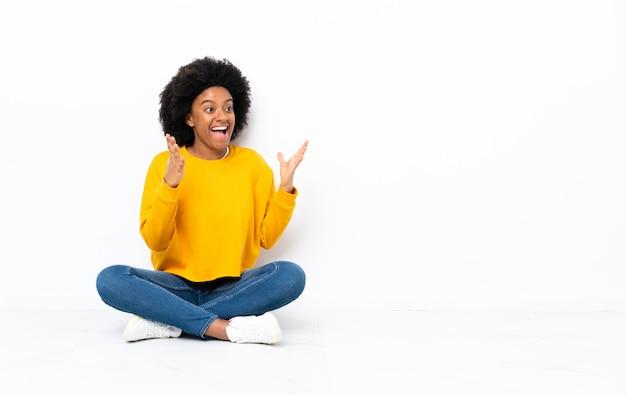 驚きの表情で床に座っている若いアフリカ系アメリカ人女性