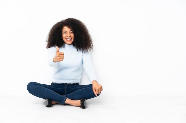 何か良いことが起こったので親指で床に座っている若いアフリカ系アメリカ人女性