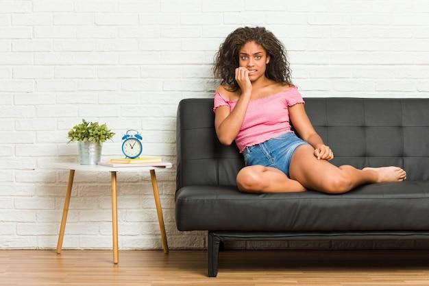 Молодая афро-американская женщина, сидящая на диване, кусая ногти, нервничает и очень тревожится.