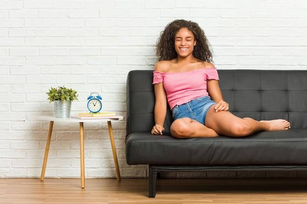 Молодая афро-американских женщина, сидя на диване, смеется и закрывает глаза, чувствует себя расслабленным и счастливым.