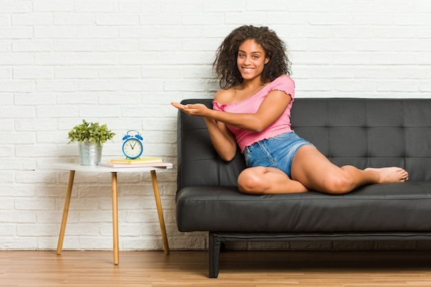 Young african american woman sitting on the sofa holding a copy space on a palm.