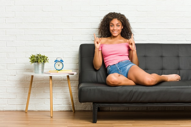 Young african american woman sitting on the sofa indicates with both fore fingers up showing a blank space.