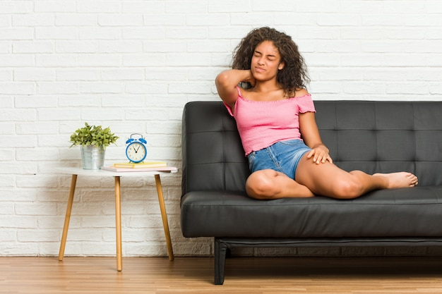 Young african american woman sitting on the sofa suffering neck pain due to sedentary lifestyle.