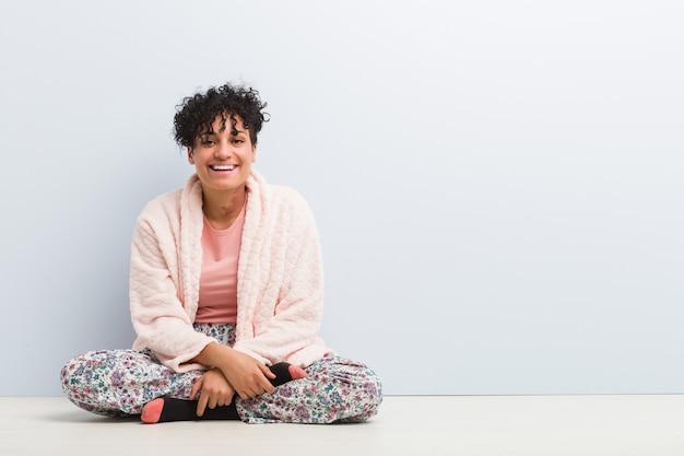 パジャマを着て座っている若いアフリカ系アメリカ人女性