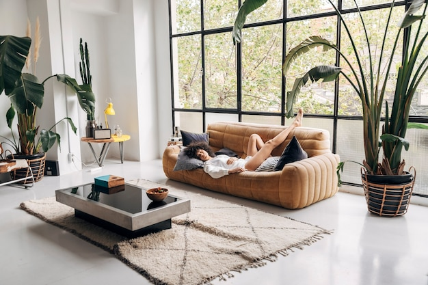 Young african american woman sleeps on a couch in a big bright living room home concept copy space