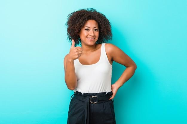 若いアフリカ系アメリカ人女性の笑顔と親指を上げる