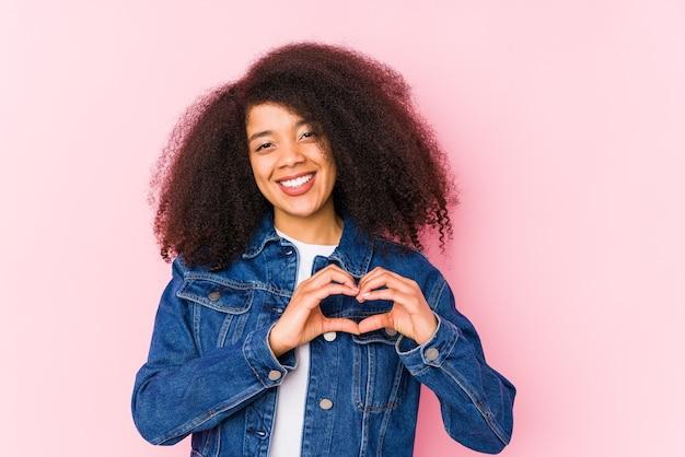 웃 고 손으로 심장 모양을 보여주는 젊은 아프리카 계 미국인 여자.