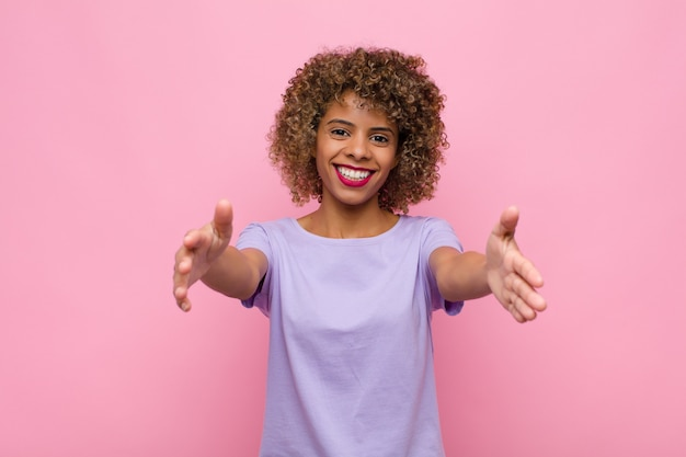 Young african american woman smiling cheerfully giving a warm, friendly, loving welcome hug, feeling happy and adorable against pink wall