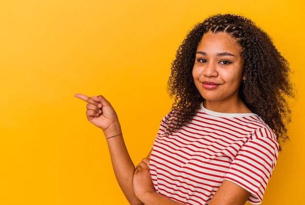 유쾌 하 게 집게 손가락으로 가리키는 웃 고 젊은 아프리카 계 미국인 여자.