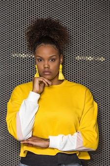 Young african american woman in stylish yellow outfit