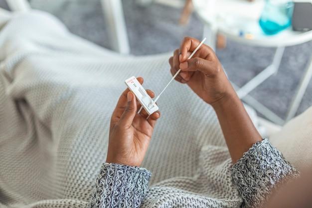 抗原キットを使用して自宅でcovid-19のセルフスワブホームテストを受けている若いアフリカ系アメリカ人女性。コロナウイルスの感染をチェックするための鼻スティックの紹介。検疫、パンデミック。