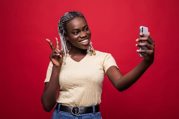 Молодая афро-американская женщина, делающая селфи на красном фоне