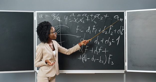 Young african american woman teacher in glasses standing at board in classroom and telling physics or geometry laws to class. teaching concept. schooling online. educative lection. math lesson.
