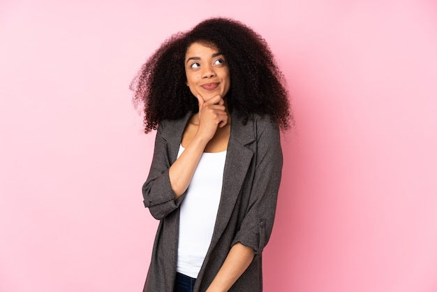 Young african american woman thinking an idea while looking up
