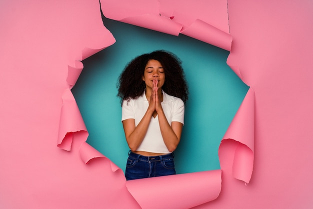 Young african american woman in torn paper isolated on blue background holding hands in pray near mouth, feels confident.