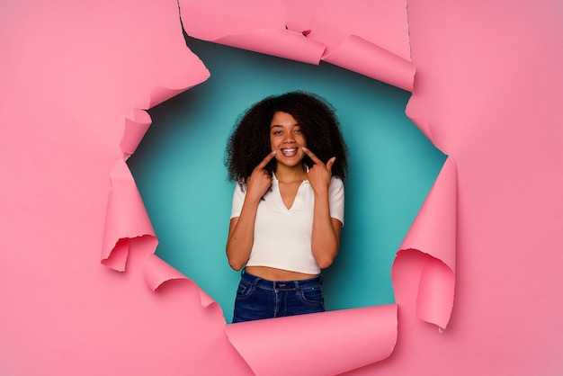 Young african american woman in torn paper isolated on blue background smiles, pointing fingers at mouth.