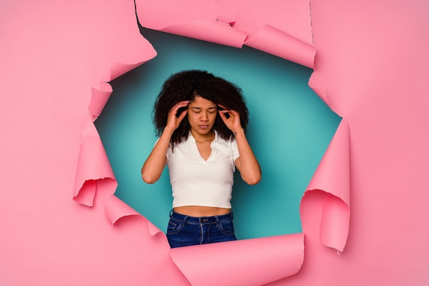Young african american woman in torn paper isolated on blue background touching temples and having headache.
