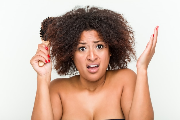 彼女の巻き毛を磨くしようとしている若いアフリカ系アメリカ人女性