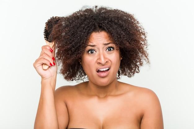 Молодая афро-американская женщина пробуя расчесывать ее вьющиеся волосы