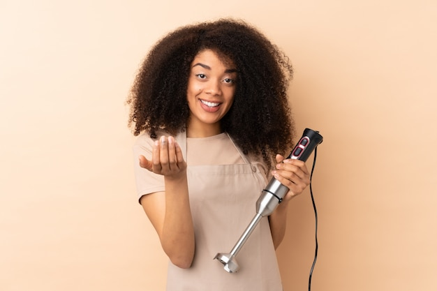 Young african american woman using hand blender on beige wall inviting to come