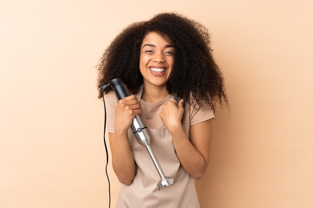 Young african american woman using hand blender isolated on beige celebrating a victory