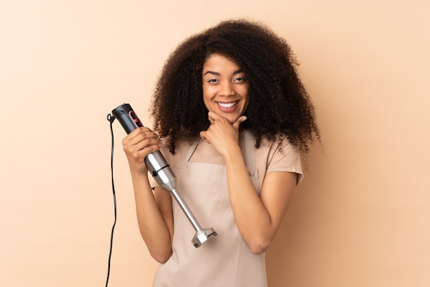 Young african american woman using hand blender isolated on beige laughing