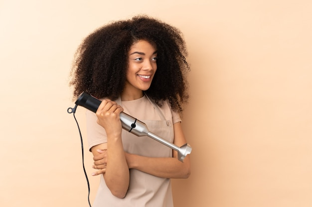 Young african american woman using hand blender isolated on beige looking to the side