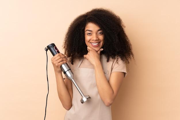 Молодая афро-американская женщина, использующая ручной блендер, изолирована на бежевом смехе
