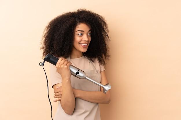 Молодая афро-американская женщина, использующая ручной блендер, изолирована на бежевом, глядя в сторону