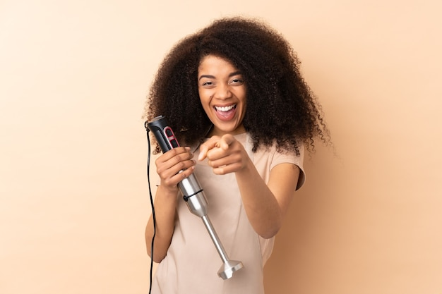 Молодая афро-американская женщина, использующая ручной блендер, изолирована на бежевом пальце указывает на вас