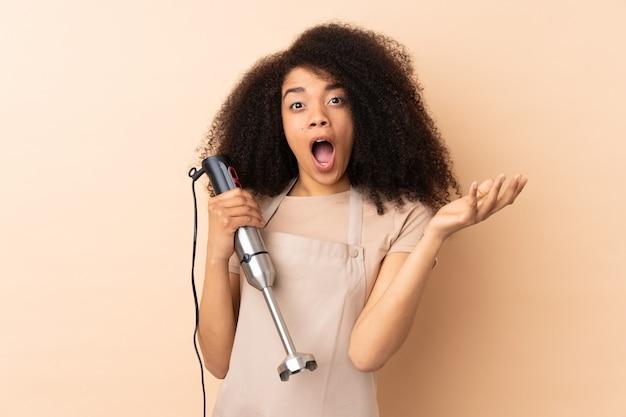 Молодая афро-американская женщина используя ручной блендер изолированный на беже с выражением лица сюрприза